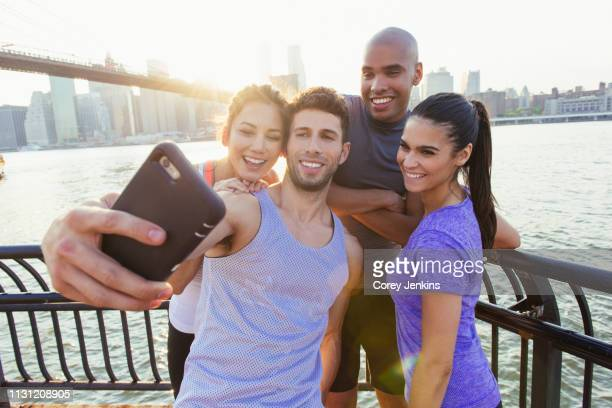 four adult running  friends taking smartphone selfie on riverside, new york, usa - international landmark stock pictures, royalty-free photos & images