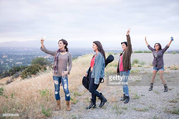 four adult sisters posing for smartphone selfie on rural hill - capturing an image stock pictures, royalty-free photos & images