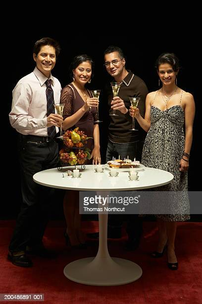 Four adults at table with champagne and cupcakes, portrait