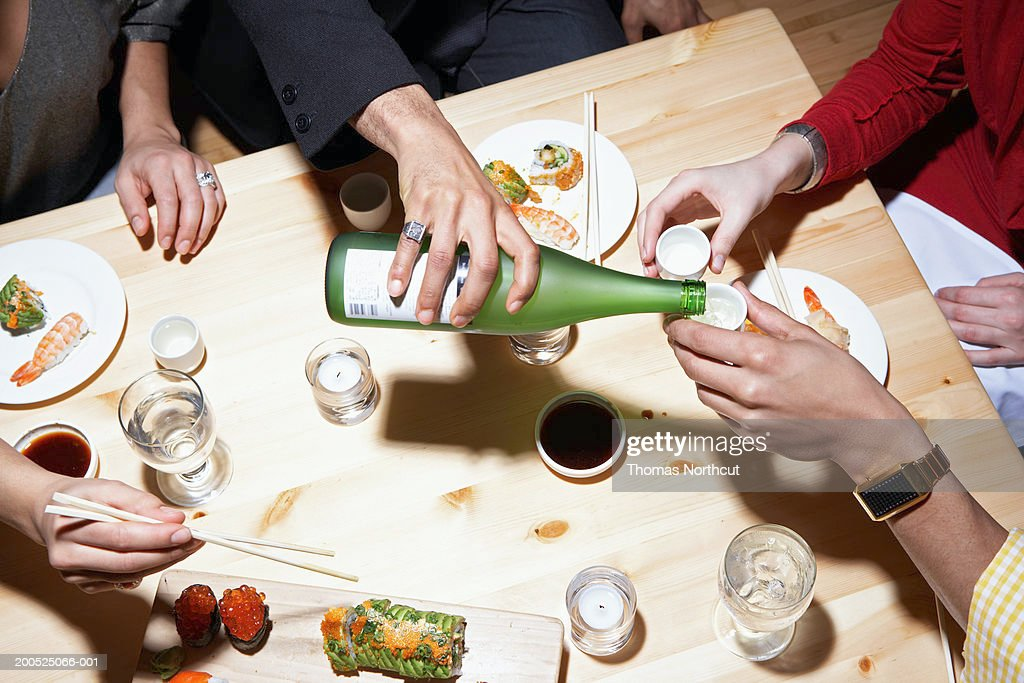 Four adults eating sushi and drinking sake, mid section, elevated view : Stock Photo