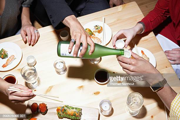 Four adults eating sushi and drinking sake, mid section, elevated view