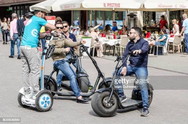 Vier Erwachsene auf Segway und elektrische Scooter in der Straße von Budapest Sommertag sprechen