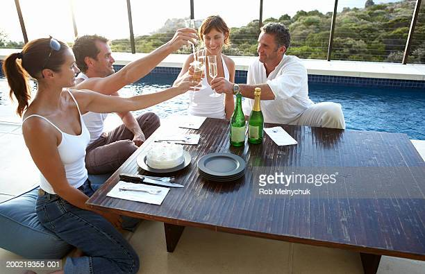 four adults toasting with champagne at table beside swimming pool - four people foto e immagini stock