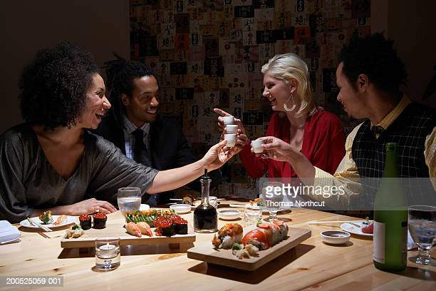 Four adults toasting with sake in sushi bar, laughing