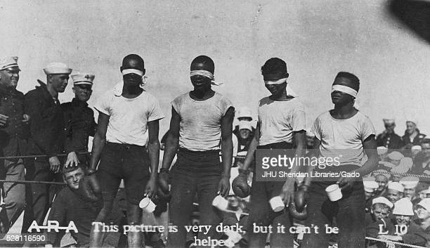 Four African American boys are standing in a boxing ring with blindfolds on each has a boxing glove in one hand and a mug in the other hand they are...
