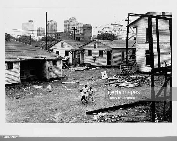 Four African American children play in a downtown slum in the shadow of high rise buildings North Carolina ca 19641968