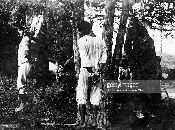 Four African American men hang from trees their hands bound behind their backs apparent victims of lynchings 1915