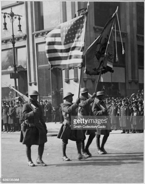 Four African American men in uniform walk in formation on the street carrying flags and guns during a parade for the famous 369th Infantry upon...