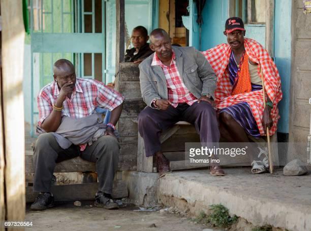 Four African men sitting in front of a house Street scene in Talek on May 17 2017 in Talek Kenya