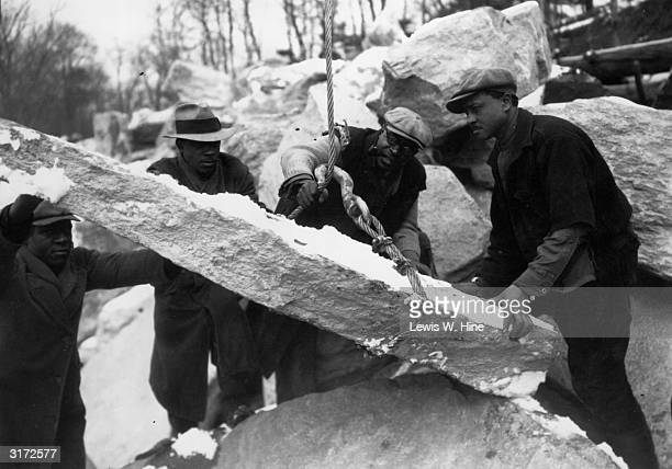 Four African-American male workers wrap a lift cable around a large slab of rock as part of the WPA work relief program, New York City.
