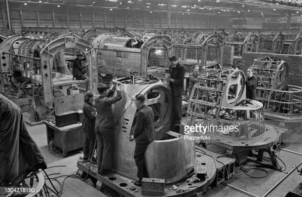 Four aircraft workers work on the fabrication of nose sections of Avro Lancaster heavy bombers under construction on a production line at an Avro...