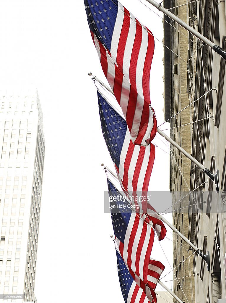 Four American flags and tall building in New York : Stock Photo