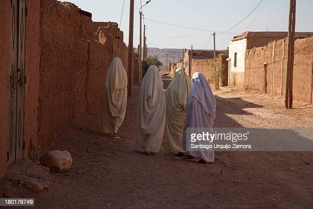 Four Arab women dressed in white robes walking early in the morning in the unpaved streets of the city of Sahli, Meknès-Tafilalet Region, Morocco.