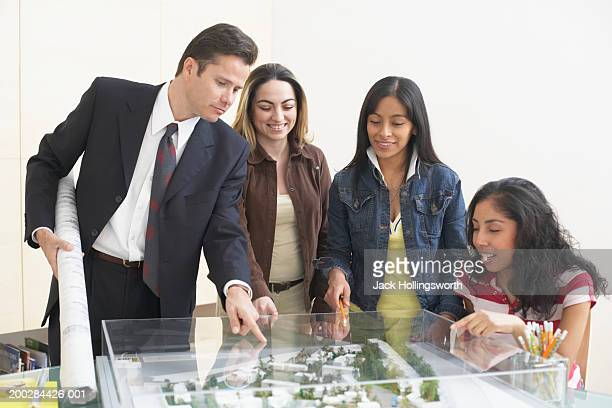 four architects looking at the model of a building complex - 建築模型 ストックフォトと画像