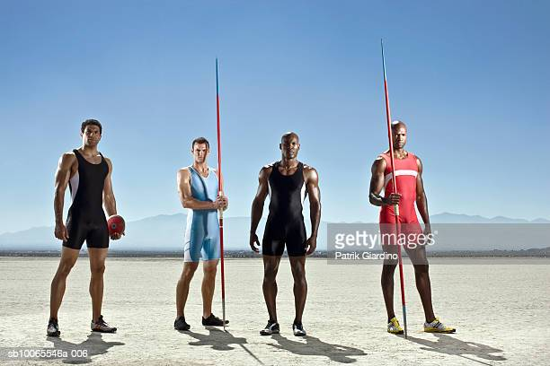 Four athletes standing on dry lake, portrait