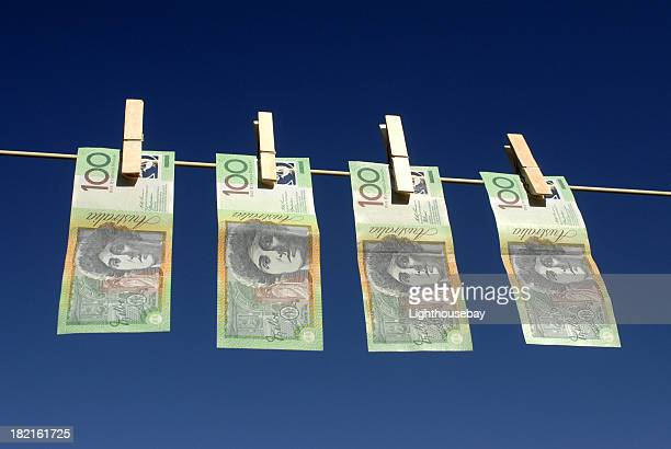 Four Australian hundred dollar notes hanging on washing line