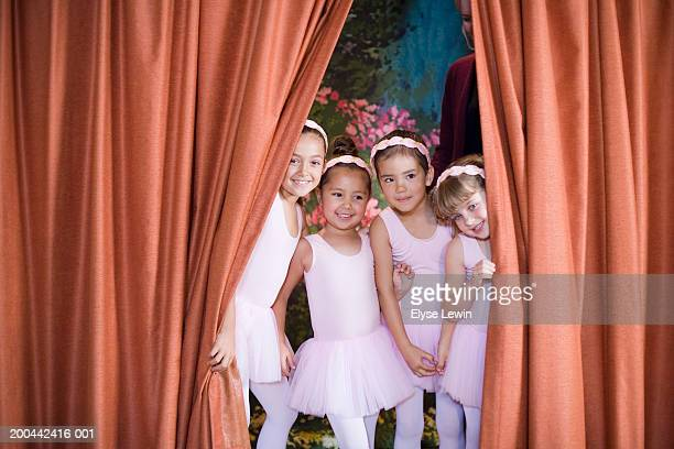 Four ballerinas (5-9) peeking out from behind curtain on stage