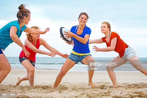 Four beautiful female friends playing beach rugby in Summer