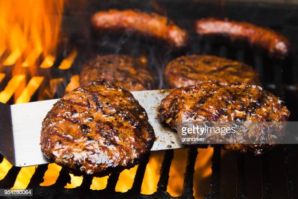 four beef burgers and two bratwursts on a hot barbeque grill - burger stock pictures, royalty-free photos & images
