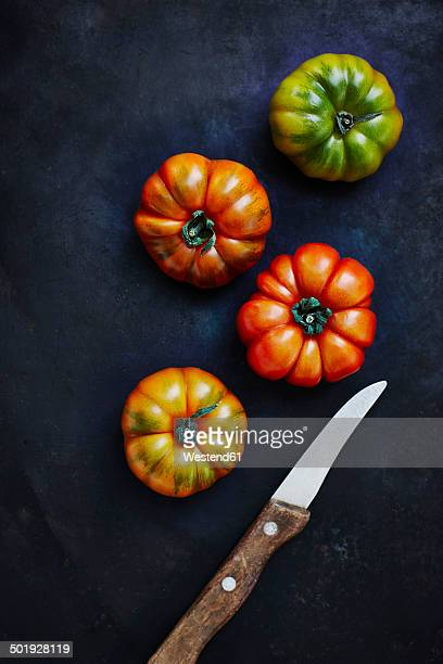 Four beef tomatos and a kitchen knife on black ground, elevated view