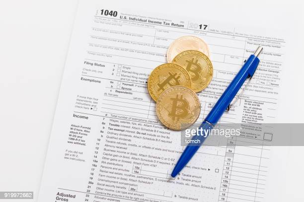 four bitcoins and a blue pen on a tax return slip - 1040 tax form stock photos and pictures