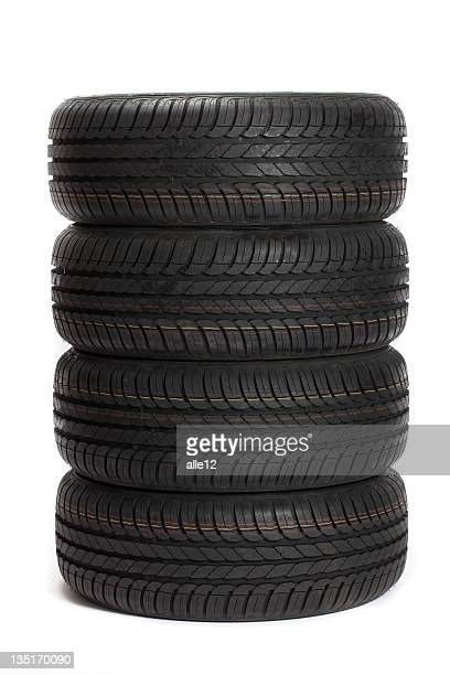 Four black car tires stacked on top of one another