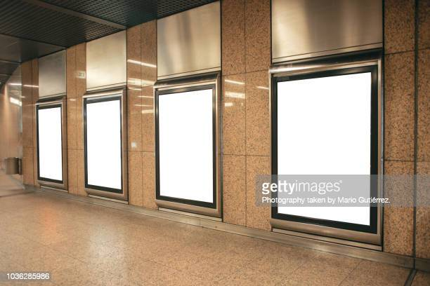 Four blank billboards at subway station