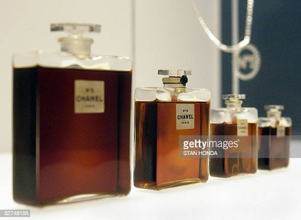 """Four bottles of Chanel No. 5 perfume by Gabrielle Chanel from 1921and a Chanel No. 5 necklace are seen at a press preview of """"Chanel"""", an exhibition..."""