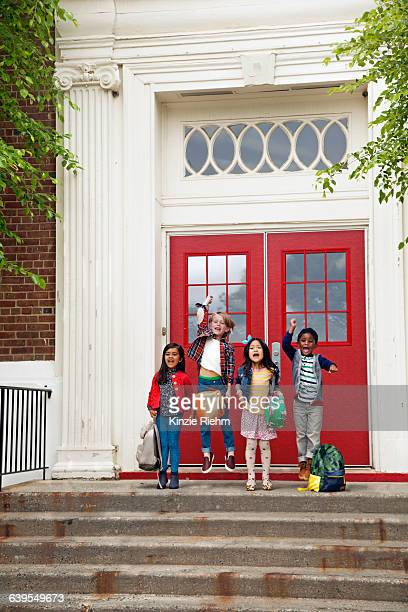 Four boys and girls jumping at elementary school entrance