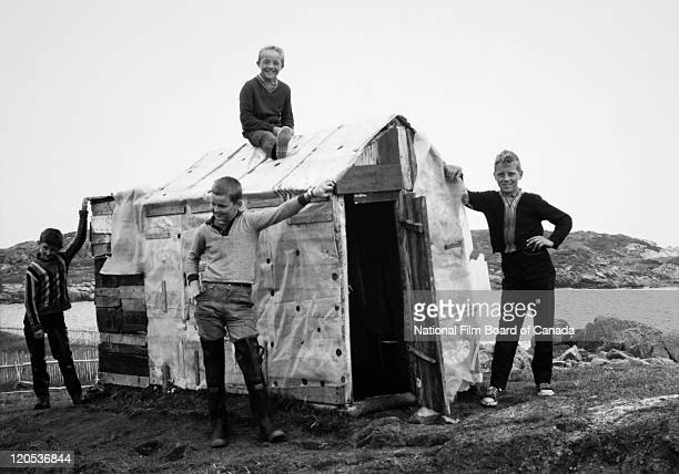 Four boys are standing proudly besides a small cabin that they've built themselves with used materials Fogo Island Newfoundland Canada August 1967...