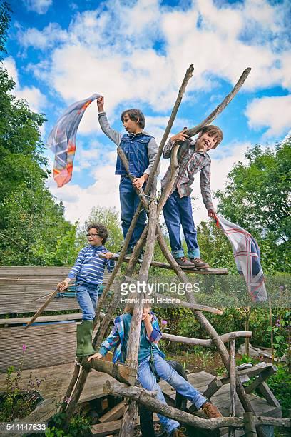 Four boys climbing on homemade climbing frame in garden