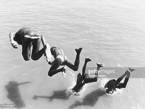 Four boys diving into the sea Mumbai Maharashtra India 1970