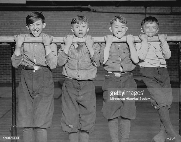 Four boys do chinups on parallel bars at the Pillsbury Settlement House