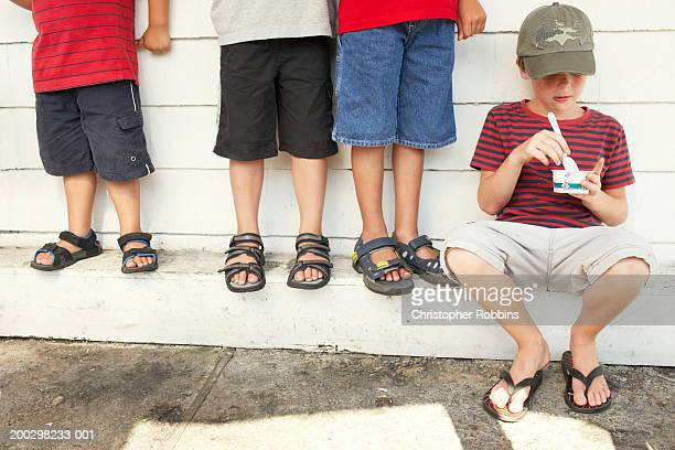 four boys (4-9) eating ice cream by wall, one sitting - sandal stock pictures, royalty-free photos & images