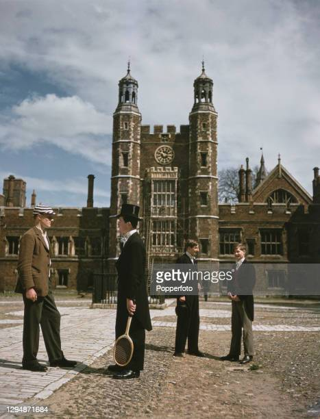 Four boys from Eton College, wearing various versions of the college uniform, stand and chat in the School Yard at the college in Eton near Windsor,...