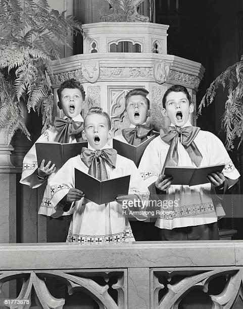 Four boys in church choir, holding books, singing hymn.