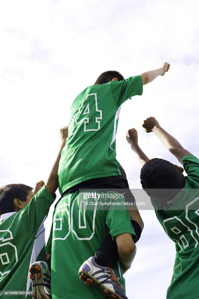 Four boys in soccer uniforms celebrating, rear view : Stockfoto