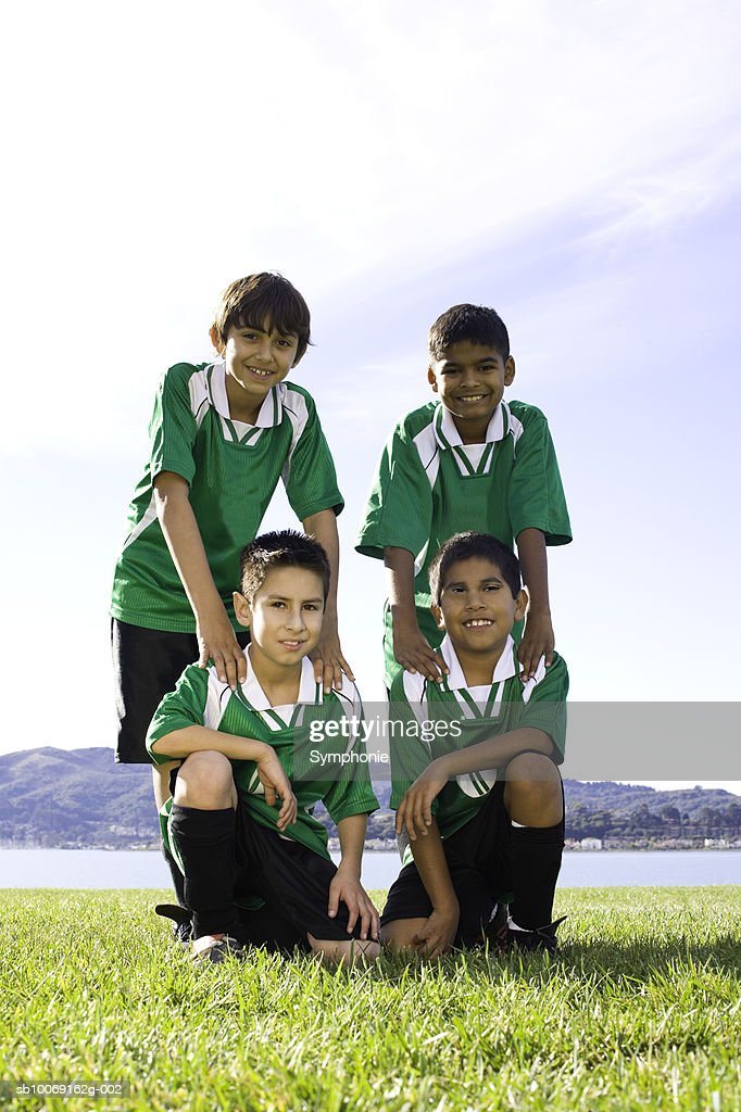 Four boys in soccer uniforms standing on field, portrait : Stockfoto