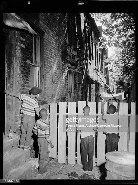 Four boys looking through fence at twostory brick row houses with collapsed wall 2519 1/2 Charles Street Pittsburgh Pennsylvania July 1957
