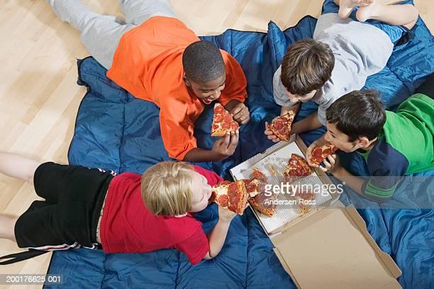 Four boys (8-11) lying on floor, eating pizza, overhead view