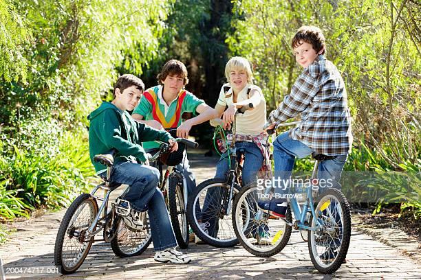 Four boys (9-13) on bikes, outdoors, portrait