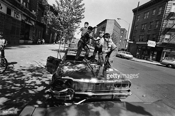 Four boys play atop the hood of an abandoned car on a street in the South Bronx New York City May 1972