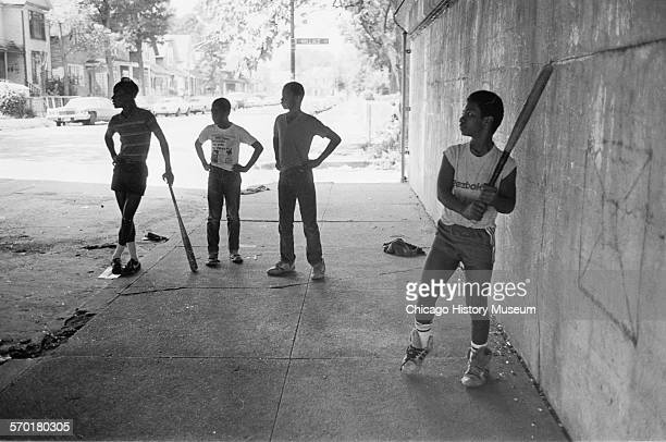 Four boys playing strikeout baseball game under the viaduct at 60th and Wallace Streets Chicago Illinois September 4 1987
