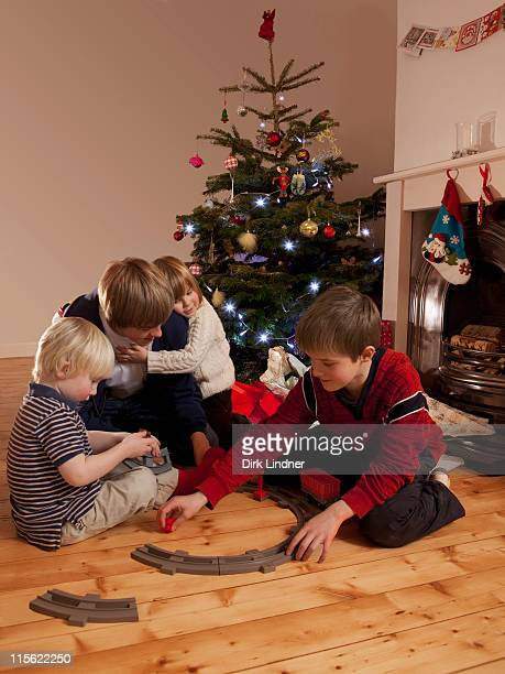 Four boys playing with a train set