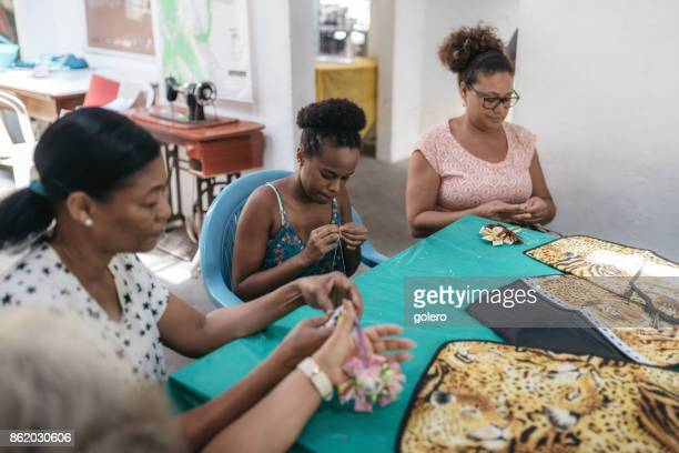 four brazilian woman sewing in tailor work room of social project