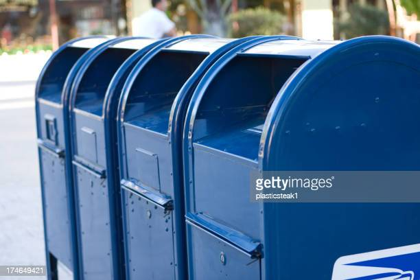 Four bright blue USPS mailboxes in a row