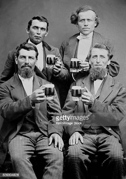 Four buddies get together and toast themselves with beer for a tintype portrait