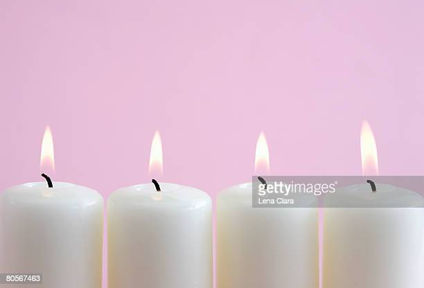 Four burning candles in a row