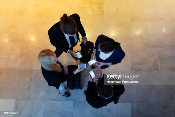 Four Business Colleagues Exchanging Contact Information