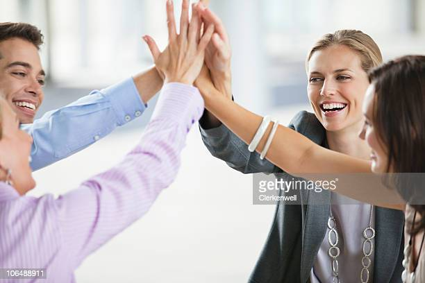 Four business colleagues giving high-five at office cafeteria